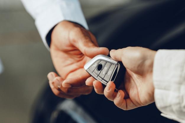 Vendedor de carros dando as chaves para um cliente de perto