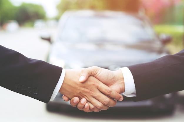 Vendedor de carros e aperto de mão do cliente