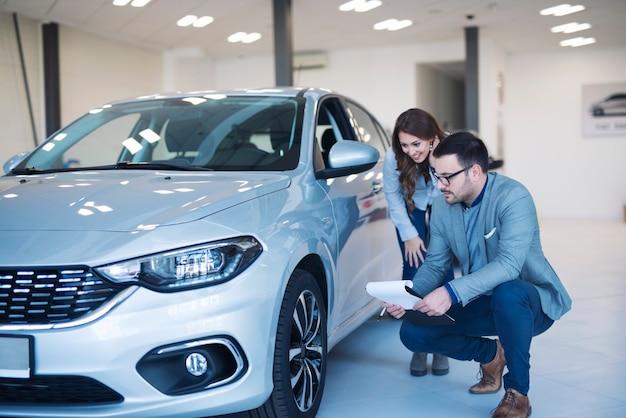 Vendedor de carros e cliente verificando especificações de automóveis na concessionária.