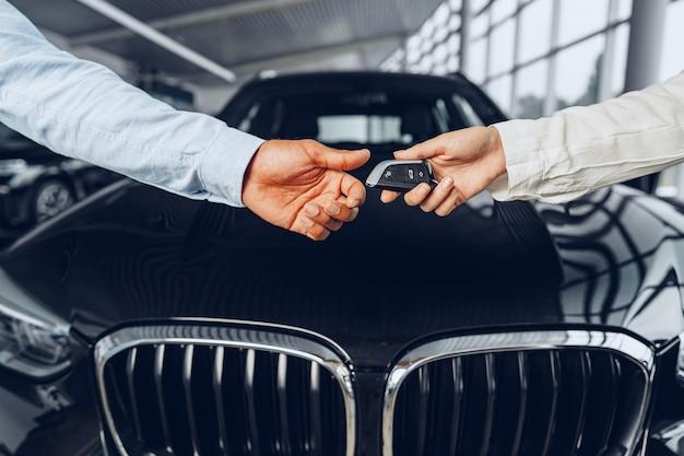 Vendedor de carros e comprador apertam a mão na concessionária contra um carro novo
