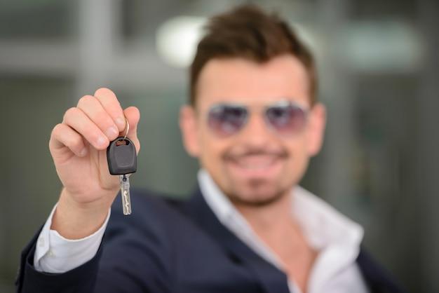 Vendedor de carros em pé na concessionária e segurando uma chave