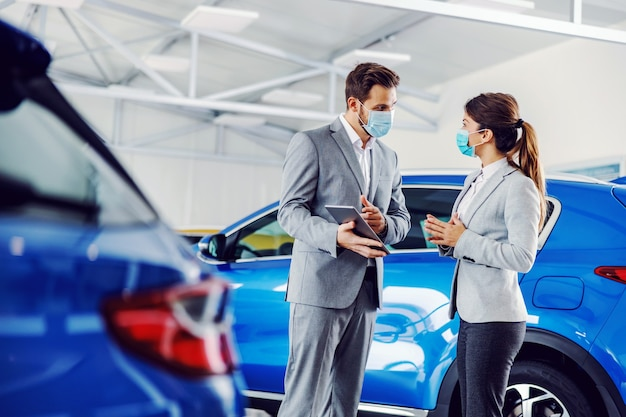 Vendedor de carros em pé no salão de beleza com um cliente usando máscaras e mostrando detalhes em um tablet.