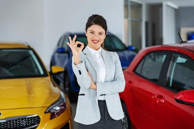 Vendedor de carros feminino sorridente em pé no salão de automóveis e mostrando sinal de tudo bem.