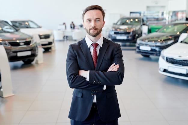 Vendedor de carros posing no showroom