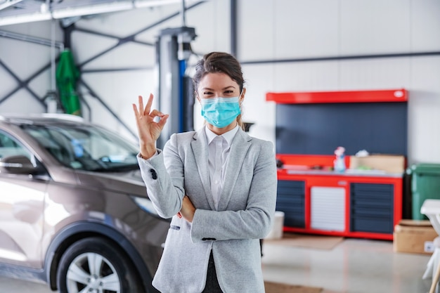 Vendedor de carros simpática e sorridente com máscara facial em pé na garagem do salão de automóveis e mostrando sinal de bom