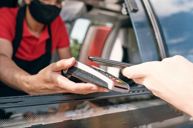 Vendedor de comida para viagem segurando o terminal de pagamento enquanto o cliente paga pelo lanche
