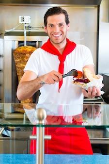 Vendedor de doner kebab em um restaurante turco de fast food, com pão sírio ou kebab feito na hora