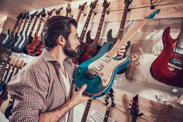 Vendedor de instrumentos coloca na prateleira elegante guitarra