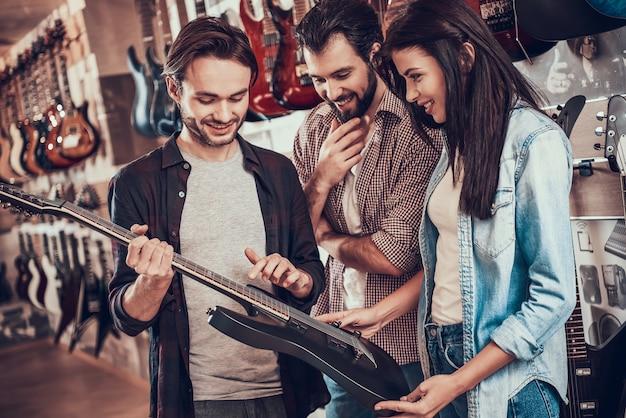 Vendedor de instrumentos musicais mostra guitarra para os compradores.