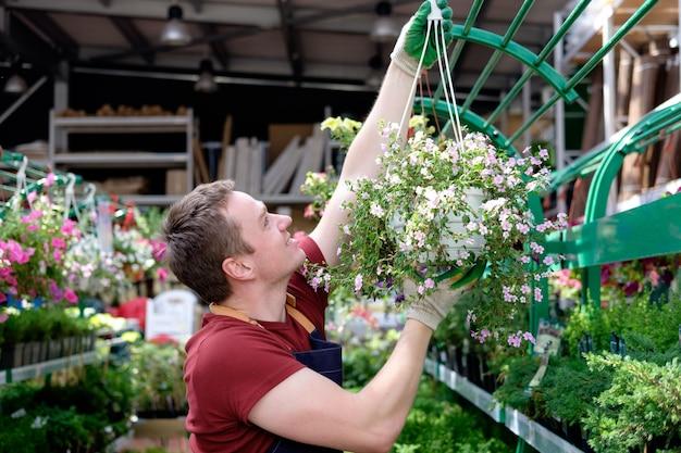 Vendedor de jovem em estufa de mercado de plantas no trabalho