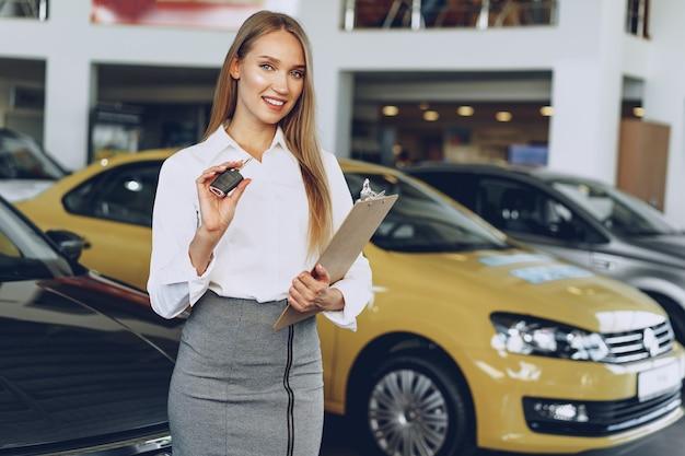 Vendedor de jovem feliz perto do carro com as chaves na mão