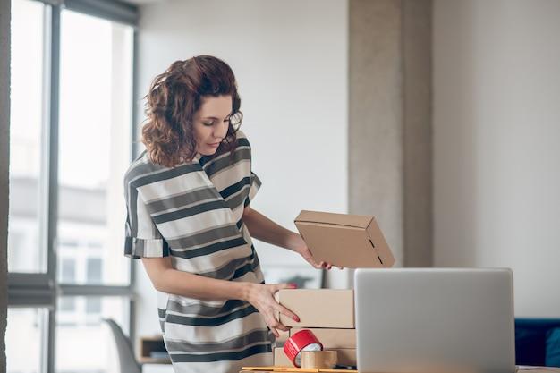 Vendedor de loja de internet focado preparando mercadorias para envio