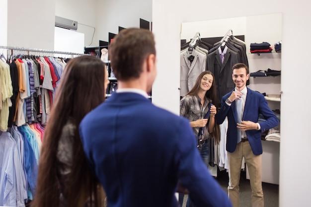 Vendedor de menina ajuda a pegar um cliente em uma boutique de roupas masculinas de gravata