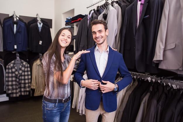 Vendedor de menina ajuda a pegar um cliente em uma boutique de roupas masculinas de jaqueta