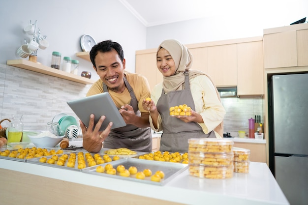 Vendedor de negócios de casal muçulmano fazendo pedido de comida em casa juntos. bolo de abacaxi de nastar