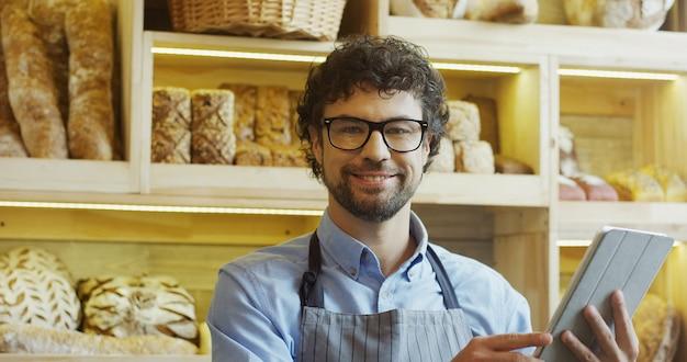 Vendedor de pão masculino atraente em copos de rolagem e gravação no dispositivo tablet em pé no balcão da loja de padaria, depois sorrindo para a câmera. dentro