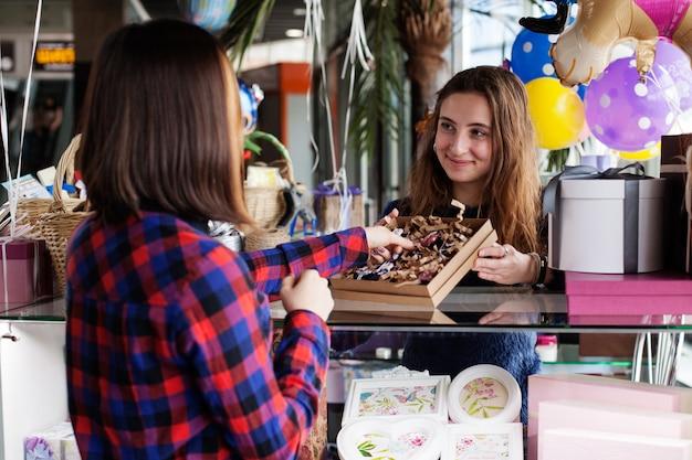 Vendedor de presente de mulher no shopping mostra mercadorias para o cliente