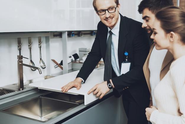 Vendedor de terno está mostrando a pia da cozinha com tampa para casal