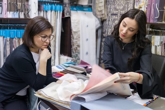 Vendedor - designer têxtil aconselha comprador de mulher