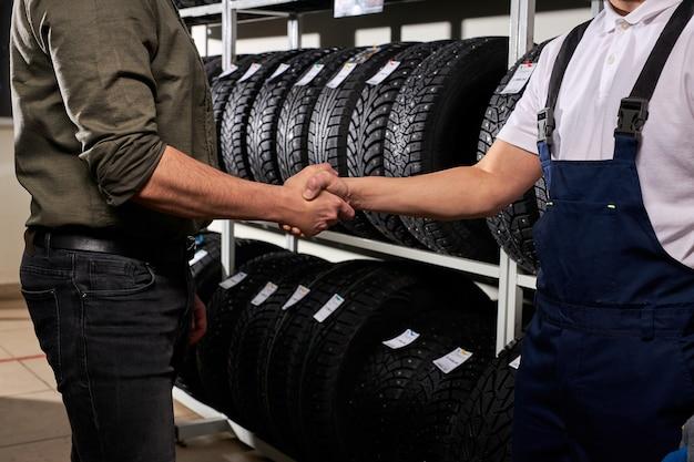 Vendedor e cliente apertando as mãos em oficina mecânica, homem fez escolha, comprando pneu de carro para o inverno