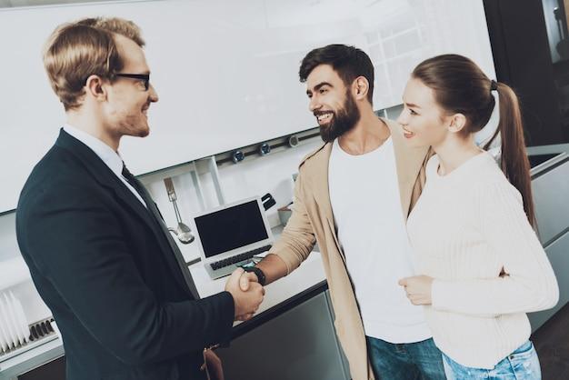 Vendedor e cliente com a esposa estão apertando as mãos na cozinha