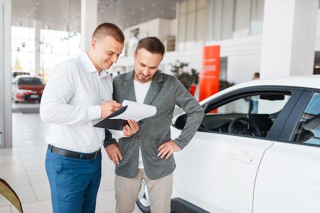 Vendedor e comprador efetuam a compra do carro novo em showroom. cliente do sexo masculino comprando veículo na concessionária, venda de automóveis