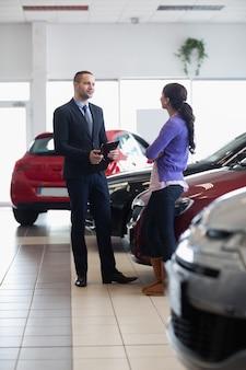 Vendedor e uma mulher falando ao lado de um carro
