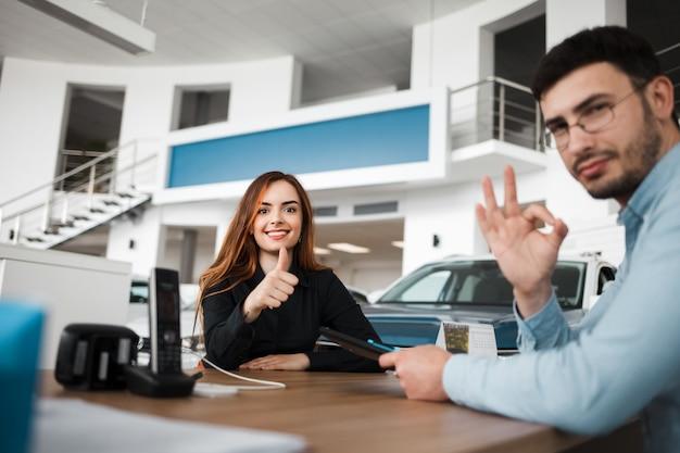 Vendedor e vendedor de carros mostram gestos ok