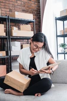 Vendedor em linha do empreendedor asiático da mulher