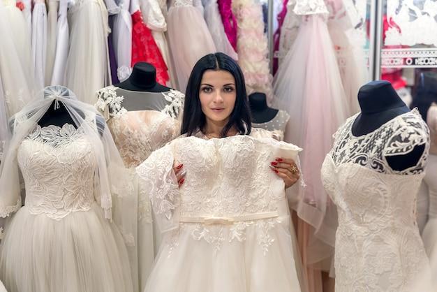 Vendedor em salão de casamento mostrando vestido de noiva