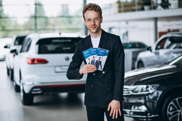 Vendedor em um showroom de carro com folhetos de negócios