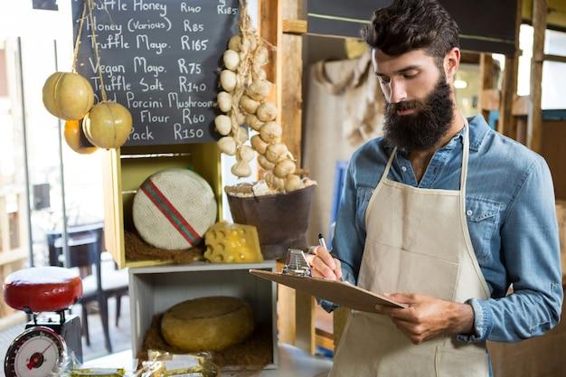 Vendedor escrevendo na prancheta no balcão de uma mercearia