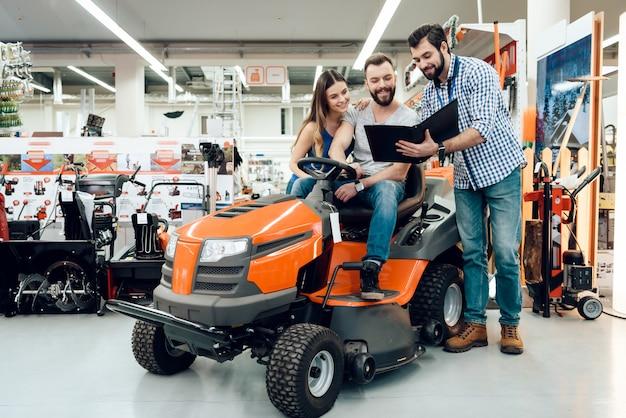 Vendedor está mostrando para casal nova máquina de limpeza na loja