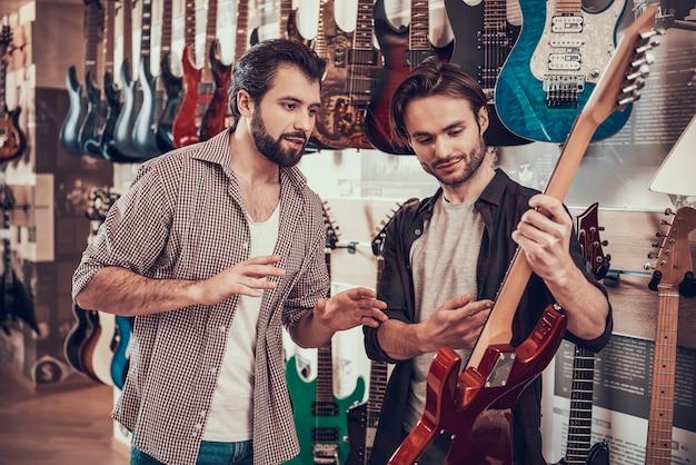 Vendedor experiente demonstra guitarra elétrica