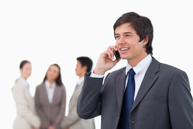 Vendedor falando no celular com os colegas por trás dele