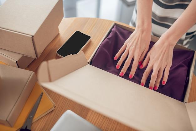 Vendedor feminino arrumando um vestido em um pacote