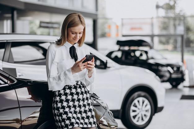 Vendedor feminino em uma sala de exposições de carro em pé ao lado do carro