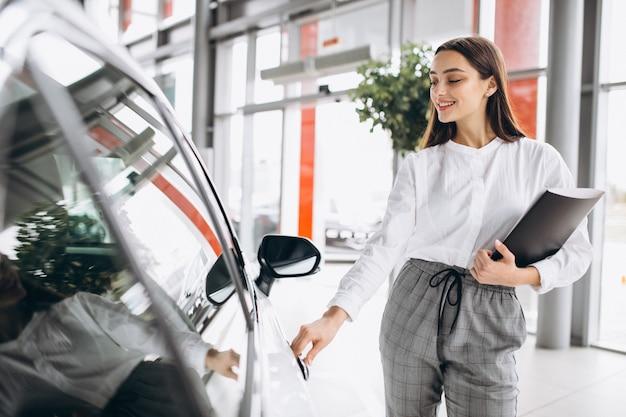 Vendedor feminino em uma sala de exposições de carros