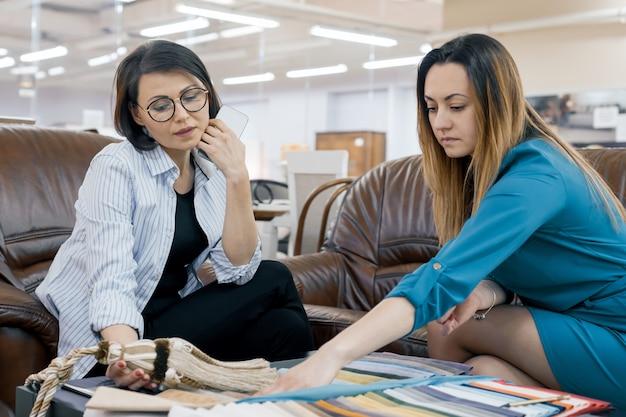 Vendedor feminino falando com o comprador na loja de tecidos