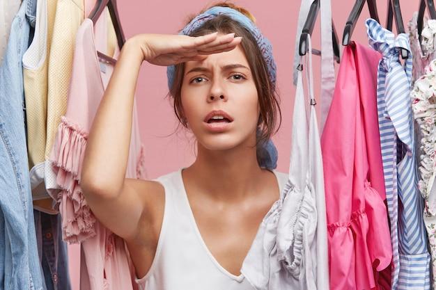 Vendedor femlae na loja de roupas, olhando para longe enquanto aguarda os clientes com grande desejo. modelo feminino atraente fazendo compras sozinho, esperando a amiga vir para lhe dar conselhos