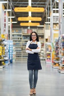 Vendedor garota feliz positivo no fundo do shopping