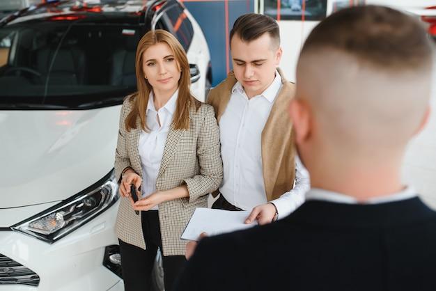 Vendedor maduro mostrando um carro novo para um casal no showroom