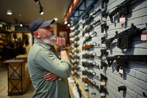 Vendedor masculino em vitrine com rifles em loja de armas
