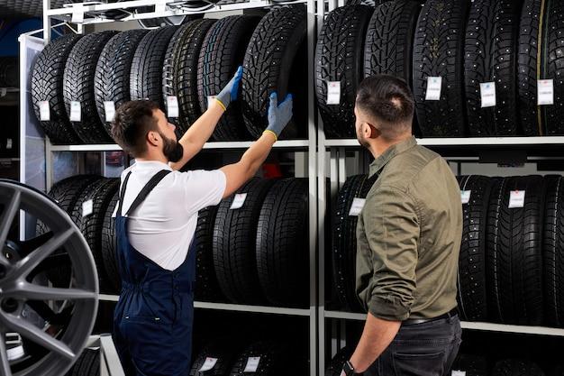 Vendedor mecânico de automóveis ajudando homem a escolher pneus em loja de automóveis, mostrando e dando informações sobre o melhor