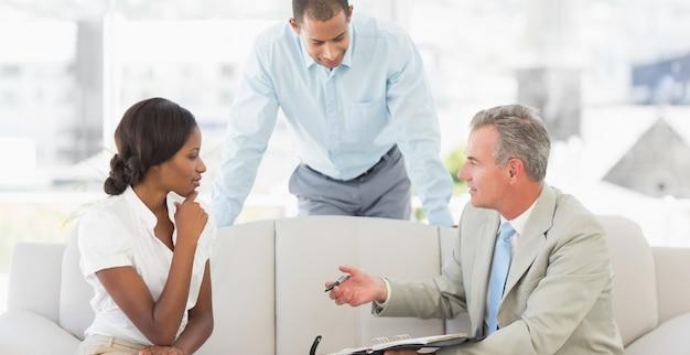 Vendedor mostrando aos clientes onde assinar o acordo