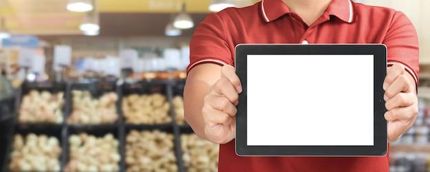 Vendedor, mostrando em branco digital tablet no supermercado tablet no supermercado