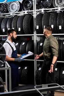 Vendedor mostrando pneus de roda para cliente homem caucasiano em serviço de conserto de automóveis e loja de automóveis. eles estão discutindo e falam sobre as vantagens dos pneus