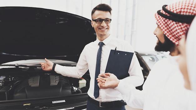 Vendedor, mostrando um carro para homem árabe