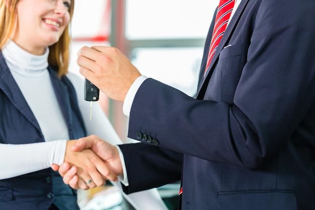 Vendedor ou vendedor de carros e cliente na concessionária, eles apertam as mãos, entregam as chaves do carro e selam a compra do automóvel ou do carro novo