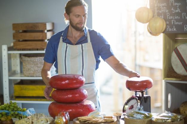 Vendedor pesando queijo gouda no balcão